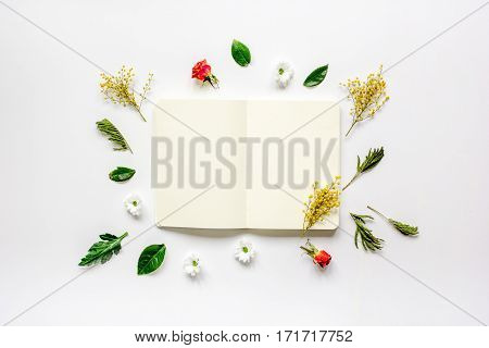 Floral flat lay with petals and opened copybook on white background top view mock up