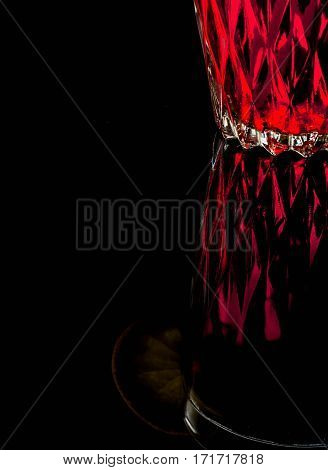 A Glass With Red Drink On A Dark Background.