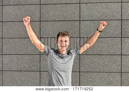 Portrait of successful male jogger with clenched fist against tiled wall