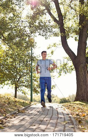 Full length of man listening music while jogging on path in park