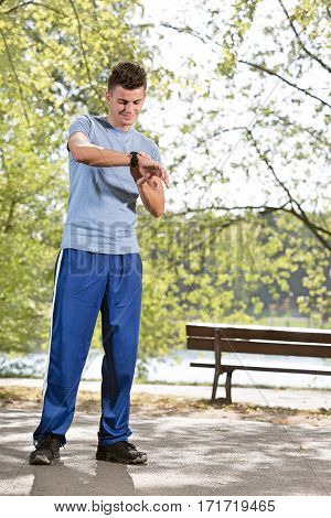 Full length of fit man checking time in park