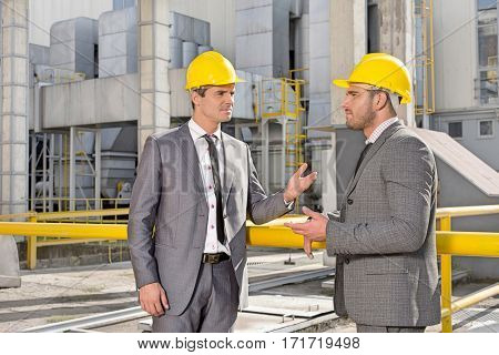 Young male engineers discussing at construction site