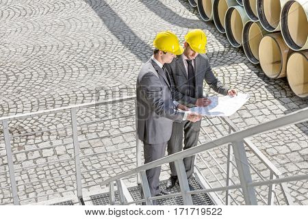 Full length of young male engineers examining blueprint on stairway