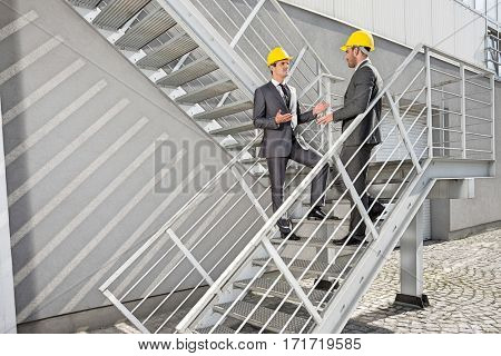 Full length of young male architects discussing on steps