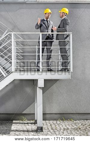 Full length of young male architects communicating on stairway