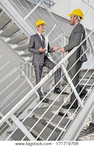 Full length of young male engineers discussing on steps