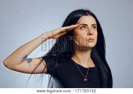Attractive young gothic girl saluting over grey background