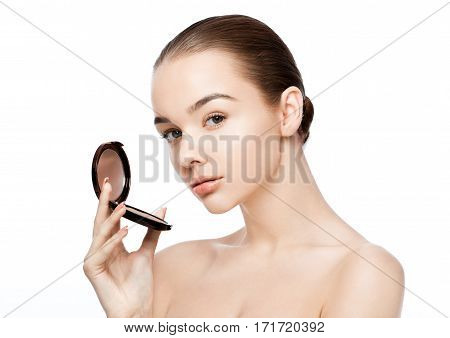 Beauty makeup model holding powder foundation container with reflection on white background