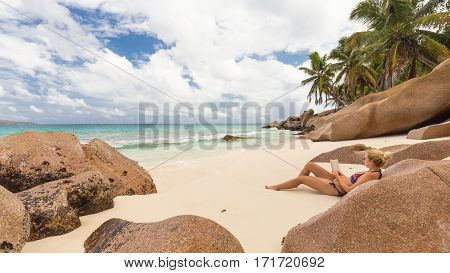 Woman reading book on perfect tropical beach of Anse Patates on La Digue Island, Seychelles. Summer vacations on picture perfect tropical beach concept.