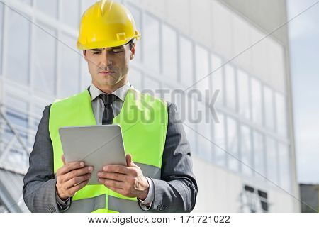 Young male engineer in reflector-vest and hardhat using digital tablet outside industry