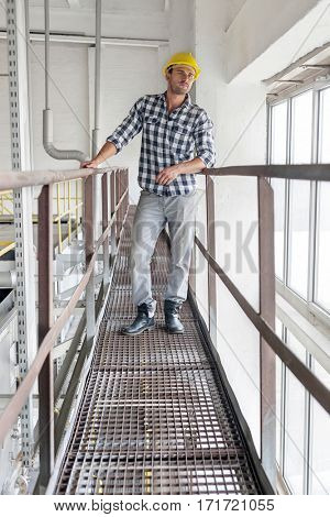 Full length of young male worker standing on metal aisle in industry