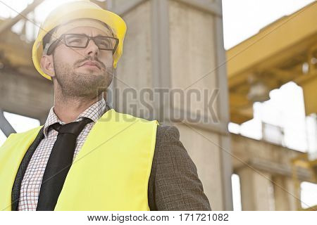 Thoughtful young male architect in protective wear at construction site