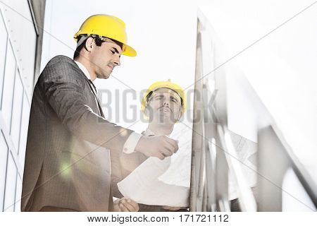 Low angle view of young businessman in hard hats reviewing blueprint on stairway