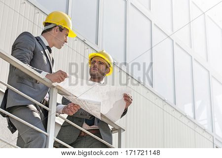 Full length of young businessmen discussing over blueprint on stairway