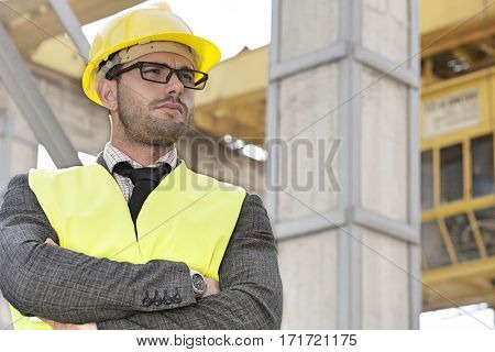 Young male architect standing arms crossed at construction site