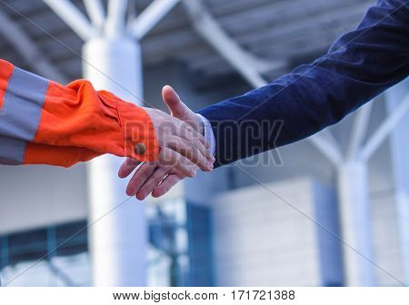 businessman handshaking with worker. Moment before handshake of suit and boilersuit. Business modern background