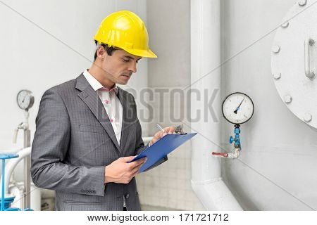 Young male supervisor inspecting pipeline in industry