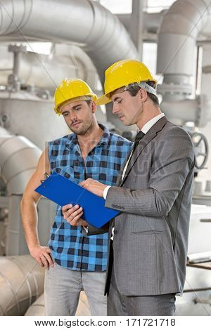 Manual worker with supervisor discussing over clipboard in industry