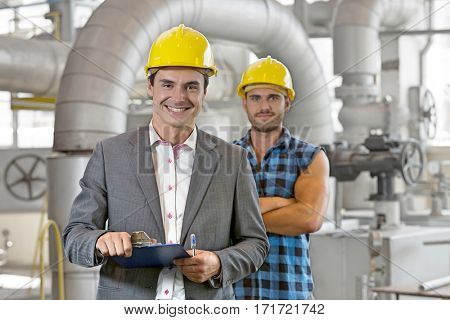Portrait of young male supervisor holding clipboard with manual worker in background at industry