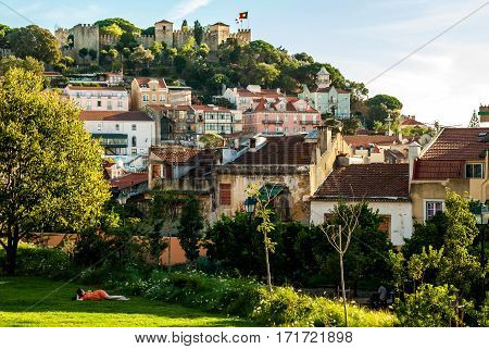 Lisbon, Portugal - Septmember 19, 2016: The new Park below the viewpoint of Graca, a woman relxing on the grass, young men sitting in the shade of the trees