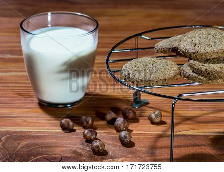 Hazelnut Cookies on a round cooling rack with Milk and Nuts at the old wooden table