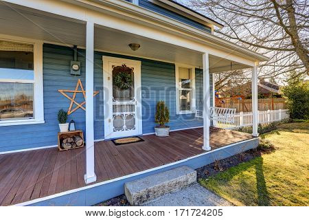 Home Exterior With Classic Northwest Charm Features Blue Siding And Wrap Around Front Porch.