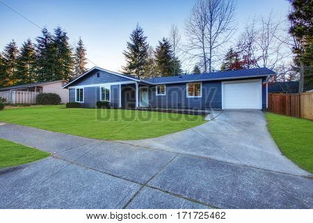 Craftsman blue one-story low-pitched roof home in Tacoma. Well kept front yard with green lawn . Northwest USA poster