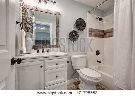 Lovely white bathroom design with reclaimed wood details. Compact bathroom features vanity cabinet with marble counter top and tub and shower combo accented with wood border. Northwest USA