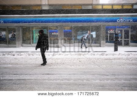 NEW YORK - FEB 9: Pedestrians walk along Broadway as snow falls on February 9, 2017 in New York. Snowfall totals of approximately six inches fell in and around NYC.