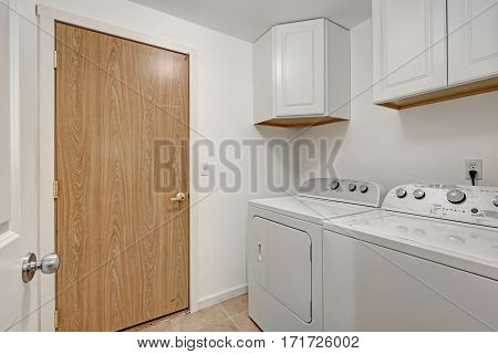 White Compact Laundry Room With Washing Machine And Dryer.