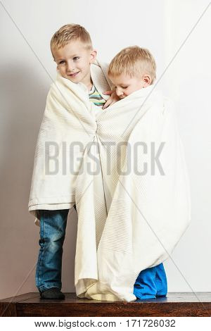 Free time fun and independence. Little boys play together indoors cover in white blanket.