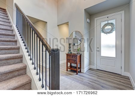 Grey Foyer With High Ceiling Over Laminate Flooring,