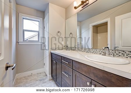 New light bathroom interior with double sink dark wood bathroom vanity accented with mosaic backsplash. Northwest USA