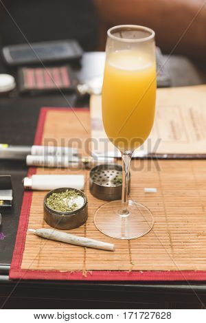 Alcoholic beverage in focus on table place mat near cannibus and related accessories.