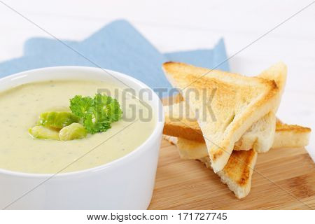 bowl of Brussels sprouts soup with toasts on wooden cutting board - close up