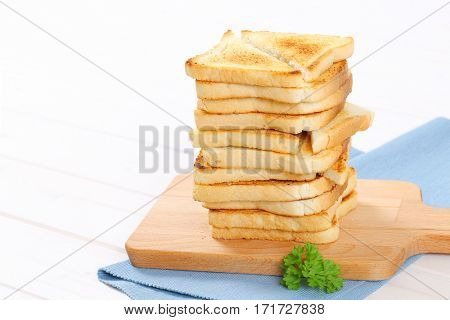 stack of toasted bread slices on wooden cutting board - close up