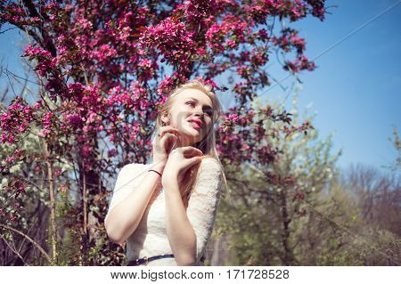 Young fashionable blonde woman in lacy white dress looking to pink cherry blossoms in the air.