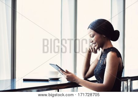 Fashionable and attractive young african woman wearing black busy looking at a digital tablet that she is holding and using on the counter next to a large birhgt window.