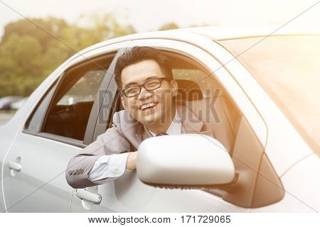Happy driver sitting in his car and smiling.
