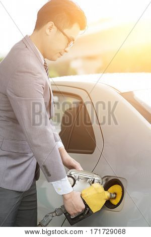 Refueling gas. Asian business man hand holding nozzle and pumping gasoline fuel in car at petrol station.