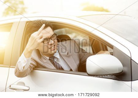 Angry rude driver showing middle finger in traffic. Negative human expression.