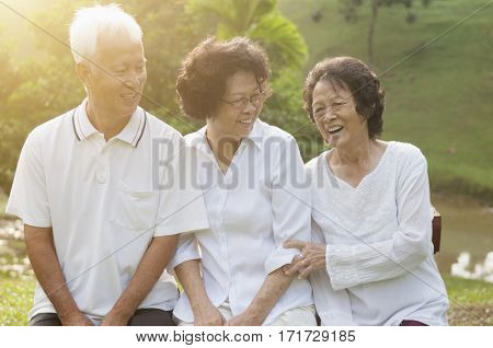 Portrait of healthy Asian seniors group having fun at outdoor nature park, in morning beautiful sunlight at background.