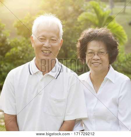 Portrait of healthy Asian seniors retiree couple having good time at outdoor nature park, morning beautiful sunlight background.