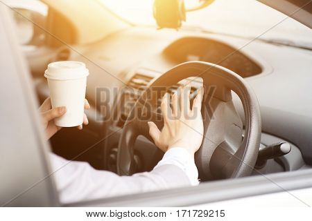 Concept photo of close up hand on steering honking while driving in morning, another hand holding coffee cup.