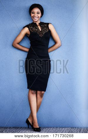 Full body image of curvy black woman smiling at the camera while wearing a beautiful black dress with her hands behind her back and her legs crossed with a blue textured background.