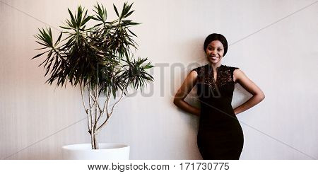 young black woman smiling while looking into camera with her hands behind her back and a pot plant next to her, as she stands against the textured beige wall.