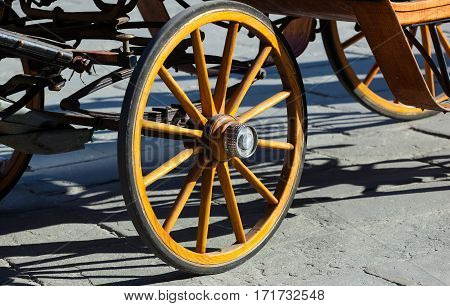 Yellow wheel olden horse carriage on the cobblestones in Florence italy.