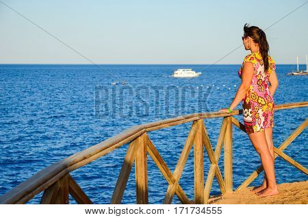Beautiful Young Girl Admiring The Sea During Sunset.