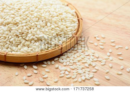 white sesame seeds in bamboo basket and wooden table