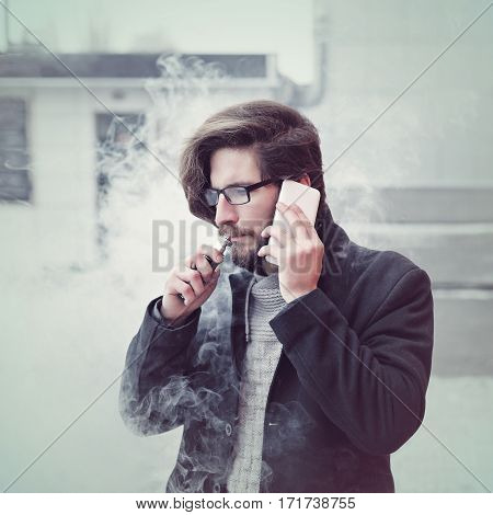 Young hipster man with a beard and glasses smokes an electronic cigarette. He says on the cell phone. Youth fashion. Delicious pairs. Cloud of steam. Business negotiations